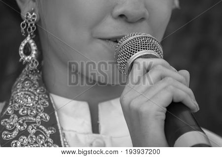 Woman hand holding a microphoneOld microphone. Vintage Style.