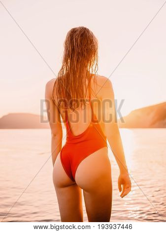 Pretty beautiful woman in red swimwear bikini posing on sea with sunset colors