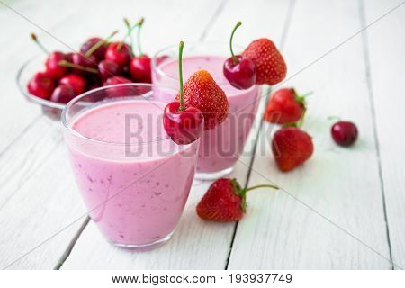 Cherry and strawberry milkshake with tasty berries in glass plate on white table. Delicious cold cocktail