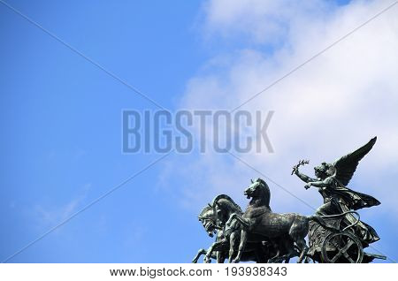 A statute of an angle in a horse drawn chariot with the sky in the background.