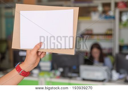 Blank white paper in the woman's hand in office.