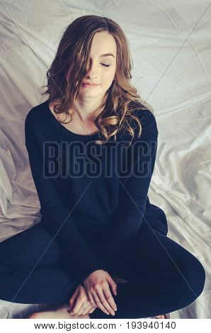 Portrait of beautiful smiling hipster teenage girl with long fair curly hair in a black jumper and pants in her apartment dreaming and looking down. Lifestyle concept.