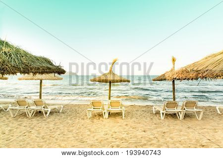 Retro look of the view from the beach with sunbeds and parasols.