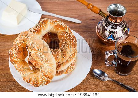 Fresh Turkish simit and a cup of black coffee. Delicious Turkish bagels with sesame seeds