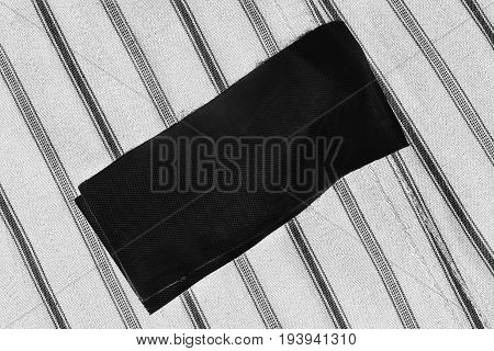 Black blank clothes label on striped white and black cloth as a background