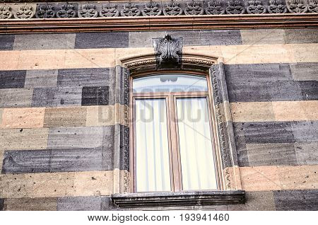 Carved stone pattern on the cornice and arched window frame with the stylized sheet ornament in the centre