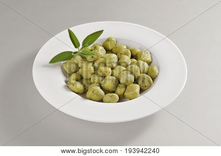 Round dish with a portion of green gnocchi isolated on grey background
