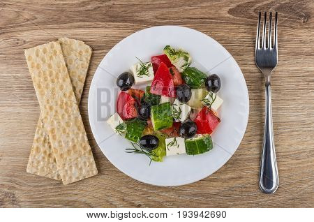 Greek Salad In White Plate, Crispbread And Fork On Table