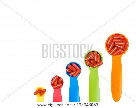 red capsules pills on colorful measuring spoon isolated on white background. Increase the dosage of the medicine. clipping path.