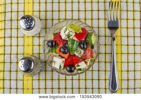 Greek Salad In Transparent Bowl, Salt, Pepper And Fork
