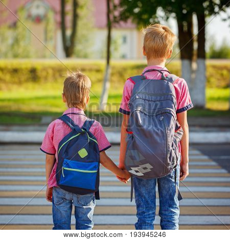 Two Kids With Backpacks Walking On The Road, Holding. School Time