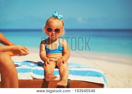 sun protection- mother applying sunblock cream on daughter at beach