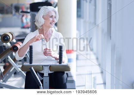 Need refreshment. Pretty elderly woman exercising on fitness equipment at gym and holding water bottle while looking through window.