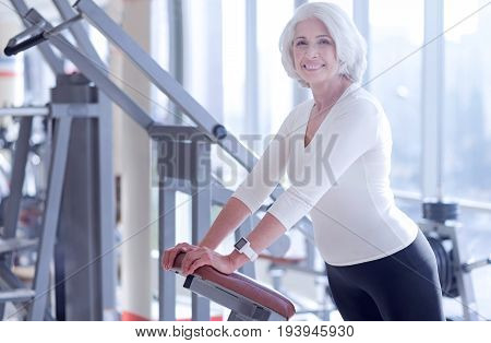 Wanna be healthier. Side view of happy pretty senior lady leaning on fitness machine at gym.