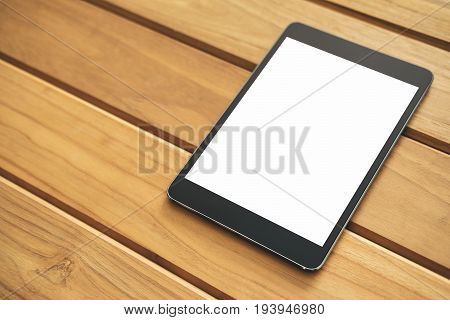 Mockup image of black tablet pc with blank white screen on vintage wooden table background