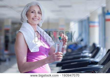 All you need. Smiling pretty senior woman covered with towel holding water bottle on race track at gym.