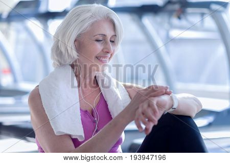High time. Close up of smiling elderly woman checking time on her wristwatch at fitness studio.
