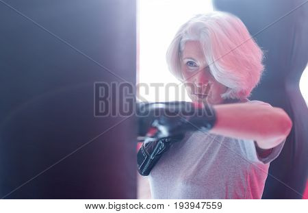 Strong hook. Close-up portrait of attractive strong aged lady standing and punching boxing bag at fitness studio.