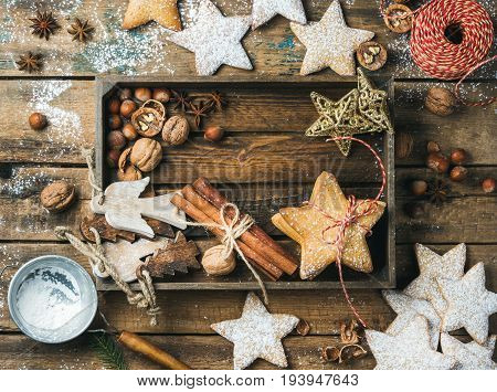 Gingerbread star shaped cookies, wooden angels, decorative stars, nuts and spices in wooden tray with sugar powder and decorative rope on wooden background, top view, horizontal composition