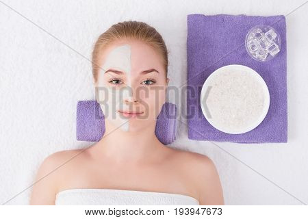 Face mask at spa salon, beauty treatment. Woman applying facial clay mask, relax, skincare, top view, overhead