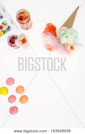 Top View Of Decorative Flowers With Macaroons And Fruity Cocktails Isolated On White