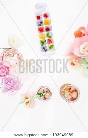 Top View Of Fruity Ice Cubes With Flowers And Refreshing Cocktails Isolated Ob White