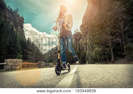 Woman on her  kick scooter on the road around mountains, under sunlight at sunny summer day.