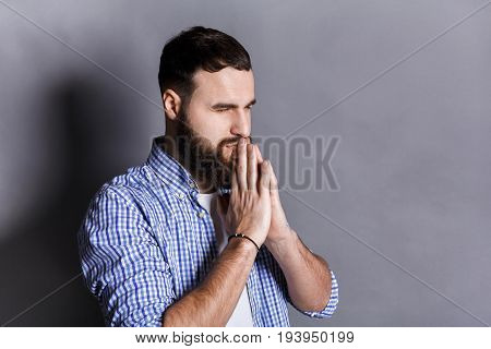 Portrait of hopeful bearded man praying. Young guy holding hands clasped near face, looking away, gray studio background