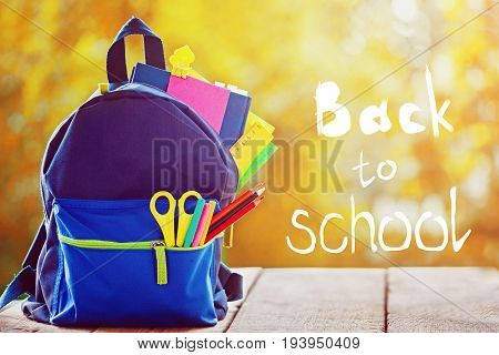 Full School Backpack On Autumn Nature Background With Word Back To School.