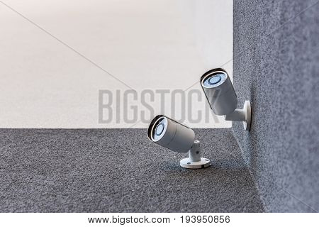 Bottom View Of Two Security Cameras On Office Building, Security System Concept