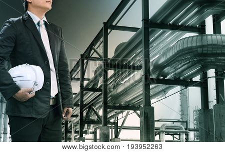 engineering man with safety helmet standing against oil refinery plant in heavy petrochemical industry estate use for fossil energy and petroleum power topic