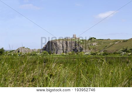 View of the Norman roofless church of St Nicholas on the hillside at Uphill village neear Weston Super Mare UK