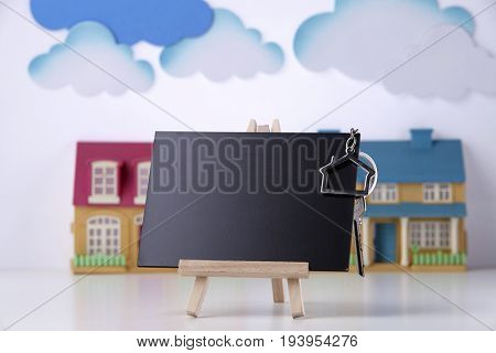 house shape key ring on the mini blackboard and model house as background