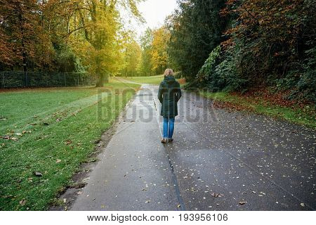 Rear view of sad melancholic woman walking in autumn park empty road walking toward sunflare
