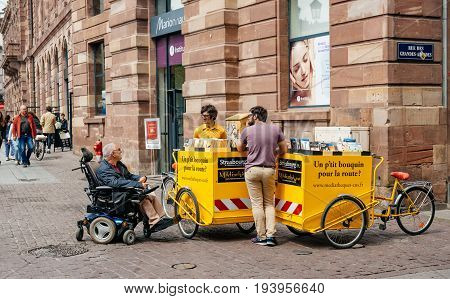 STRASBOURG FRANCE - MAY 18 2016: Man in wheelchair renting a book from the mobile bibliophile Discotheque in central French city of Strasbourg