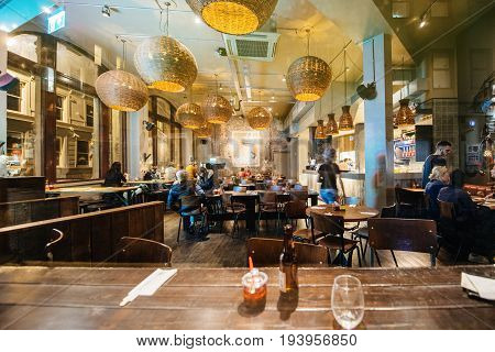 BRISTOL UNITED KINGDOM - MAR 5 2017: Interior of traditional England bar pub restaurant at night full with people enjoying delicious food and drinking beer in the city of Bristol - view through street glass