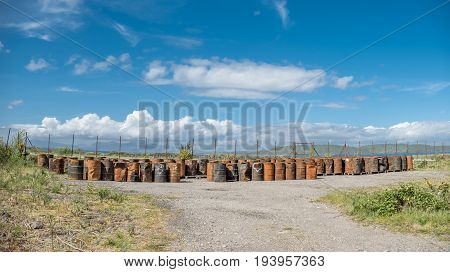 Rusty fuel and oil casks stored at an fence, Argyll, Scotland