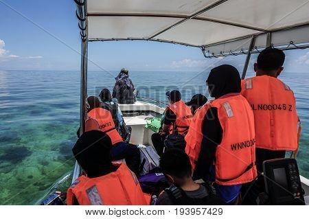 Labuan,Malaysia-May 1,2017:Group of people on the boat visiting to the Rusukan Besar island in Labuan,Malaysia.It is very popular place for tourist to visit & snorkeling underwater in Labuan.
