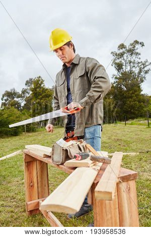 Lefthanded carpenter cutting wood in forest with saw