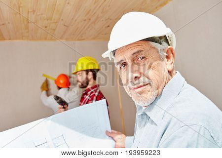 Senior citizen as foreman with floorplan planning with experience