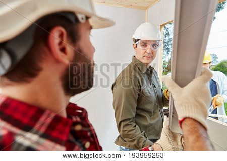 Mechanic team working at construction site installing window