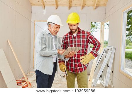 Craftsmen with tablet computer during building construction