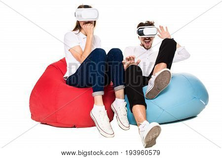 Excited young couple experiencing virtual reality seated on beanbags isolated on white background. A young couple, both in jeans, white sneakers and T-shirts. VR