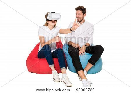 Smiling friends experiencing virtual reality glasses seated on beanbags isolated on white background. Experiencing virtual gaming adventure. VR