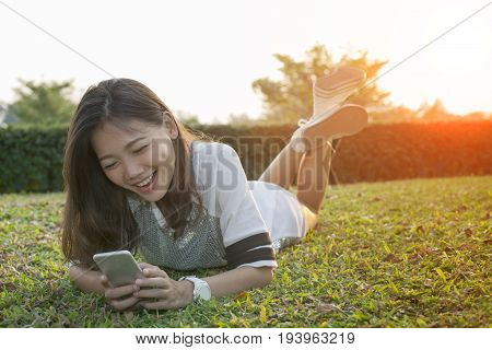 asian younger woman lying on field playing smart phone and laughing