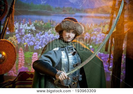 A woman dressed in chain mail cloak and fur hat with a scimitar in her hands against the background of field with flowers river and mountains in the distance