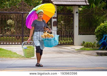 KHAO LAK, THAILAND - NOVEMBER 5, 2012: Local woman carrying bread on the local market in Khao Lak. This market is also tourist attraction in Phang Nga province of Thailand