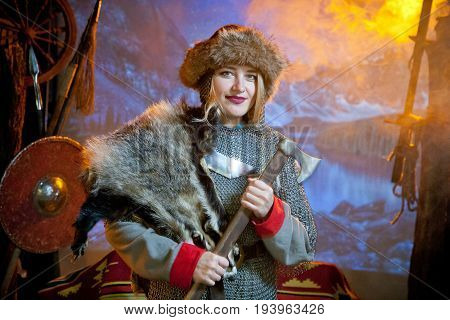 A smiling woman dressed in chain mail and fur with an ax in her hands against the background of arms and mountains in the distance