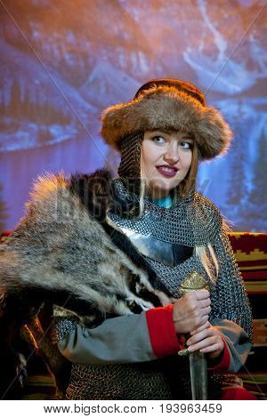 A smiling woman dressed in chain mail and fur with a sword in her hands against the background of mountains in the distance