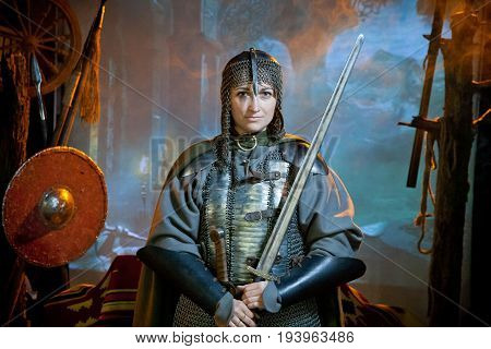 A woman dressed in chain mail with a sword in her hands against the background of of the castle weapons and mountains in the distance